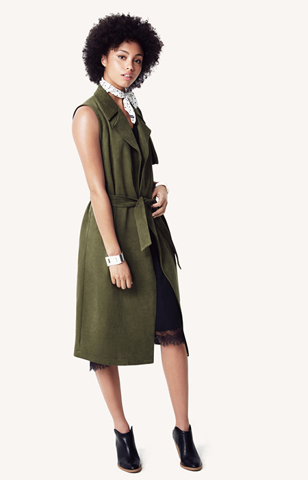 A model in a green sleeveless dress and white dotted neck scarf