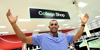 Grant Hill poses in front of a College Shop sign