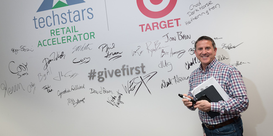 Brian Cornell signs a wall covered in Target + Techstars logos and signatures.