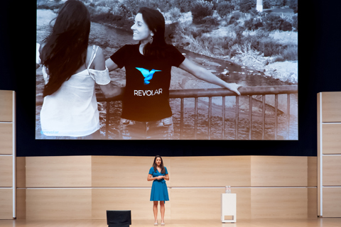 Jackie from Revolar makes her Demo Day pitch on stage, in front of a photo of her and her sister