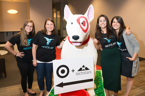 The Revolar team, in black branded t-shirts, poses with a Bullseye dog made of Legos