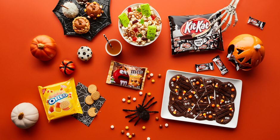 A display of candy and snacks against an orange background.