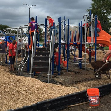 Several volunteers build a jungle gym