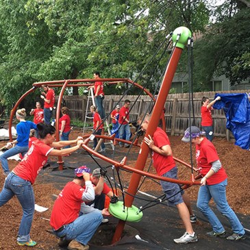 A group of volunteers construct a piece of playground equipment