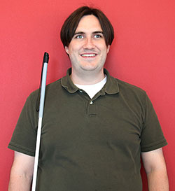 Accessibility lead Ryan Strunk, wearing a green shirt and standing in front of a red background.