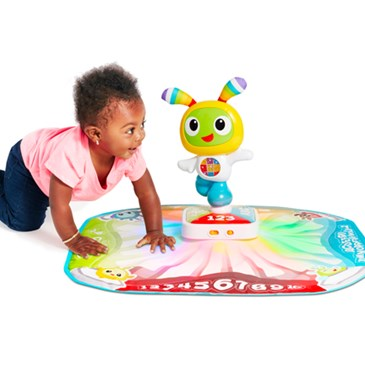 A little girl plays on the colorful dance mat