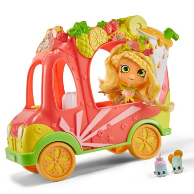 A pink, citrus-y smoothie cart is driven by a blonde doll