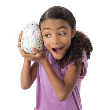 A little girl holds a large, blue and green speckled egg