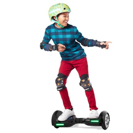 A boy wears a helmet as he rides the black and green hover board.