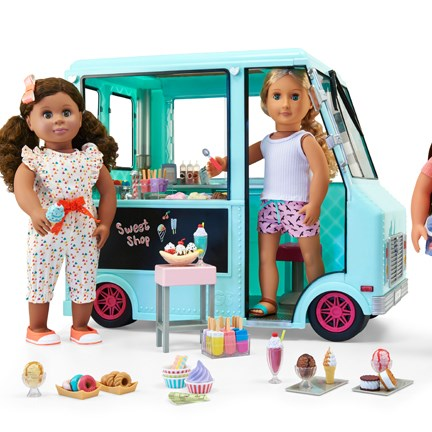Three Our Generation dolls enjoy treats in front of a teal ice cream truck.