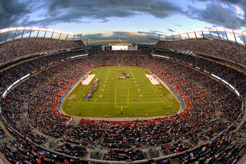 The sun sets over Mile High Stadium during a football game