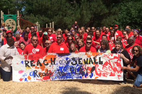 "A huge crowd of Target volunteers poses on the new playground with a colorful ""Reach Sewall"" sign"