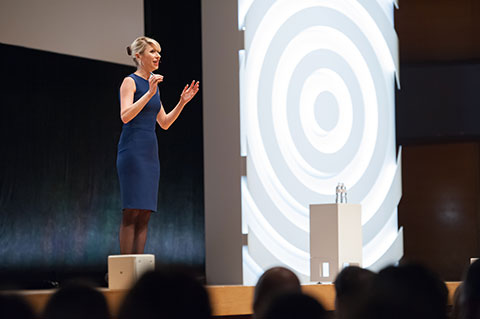 Amy Cuddy onstage, arms raised to demonstrate a power pose
