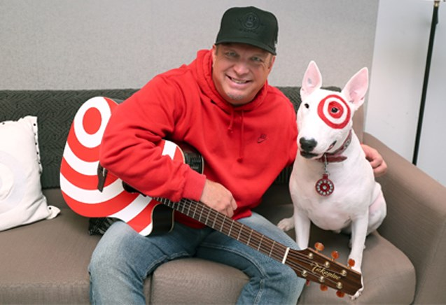 Garth Brooks wears a red sweatshirt as he holds a red branded guitar and poses with Bullsye the dog