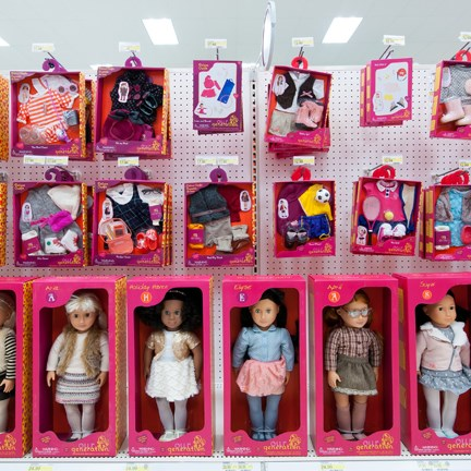 A variety of dolls are lined up in a row, with outfits above