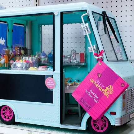 A teal, doll-sized ice cream truck with pink Our Generation tag