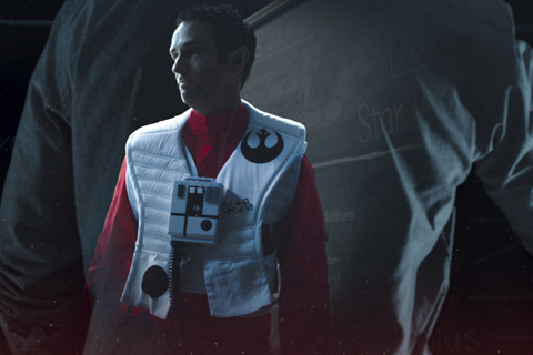 Dan, dressed in a red and white X-wing pilot suit, looks into the distance.