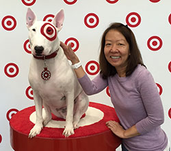 Head-and-shoulders shot of Maria Elisa next to Bullseye the dog