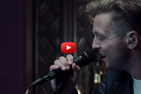 A close-up of Ryan Tedder singing into a microphone