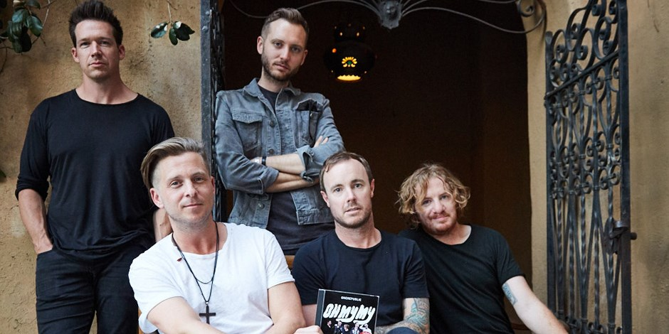 The men of One Republic pose for a picture with their album cover.