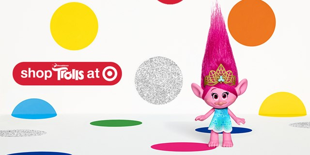 "A Poppy figurine stands in front a of colorful, polka-dot background, w/ ""Shop Trolls at Target"""