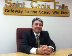 Brian Blesi at his desk, behind him, the text Saint Croix Falls, Gateway to the Scenic Wild River.
