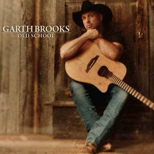 Garth holds a guitar in front of a wood grain background