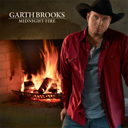 Garth, in a black cowboy hat, stands in front of a fire
