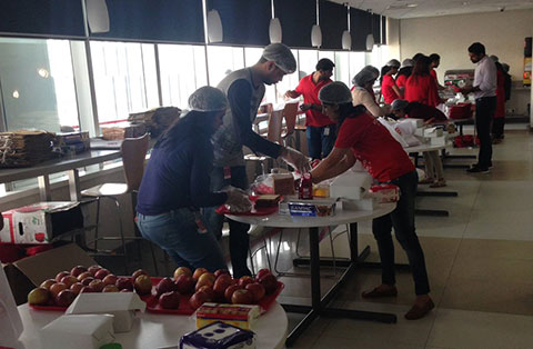 Volunteers assemble care packages with food and supplies to donate to their community