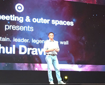 Rahul stands onstage in front of a large screen at his Outer Spaces talk