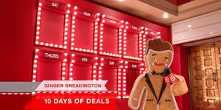 Ginger Breadington with mic in front of 10 Days of Deals lineup