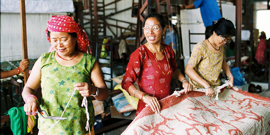 Three women weaving rugs at a factory. Photo © U. Roberto Romano, courtesy of GoodWeave
