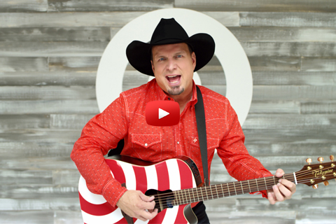 Garth performs with a red and white guitar in front of a white bullseye