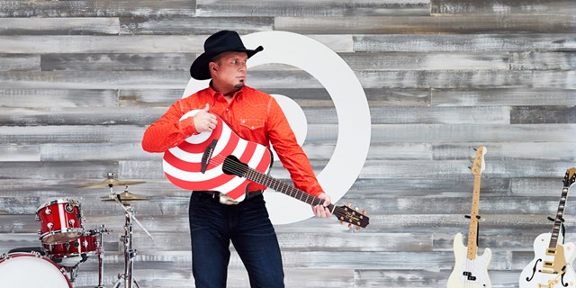Garth Brooks holds a red and white guitar against a white bullseye background