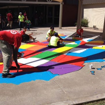 Team members paint a giant U.S. map on the pavement
