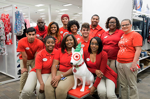 Twelve Baton Rouge team members in red and khaki pose together with a statue of Target's mascot, Bullseye the dog