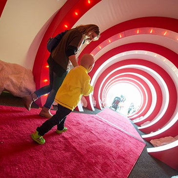 A parent and child enter the event through a winding lit-up tunnel