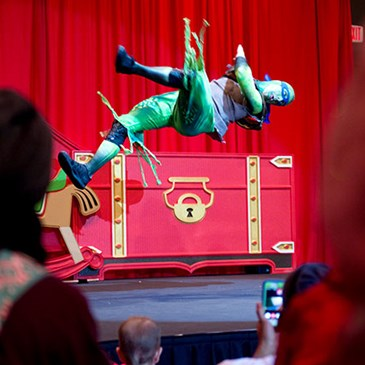 A performer dressed as a Ninja Turtle does a flip onstage