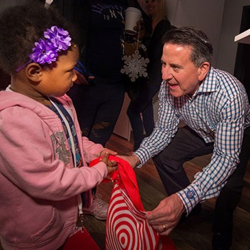 CEO Brian Cornell hands a kid a gift bag