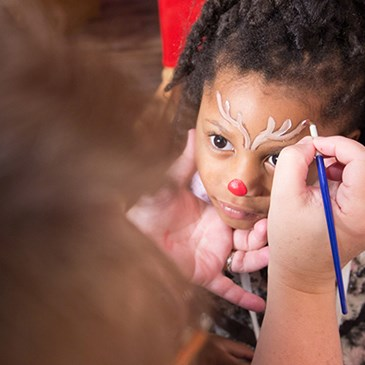 A little girl gets her face painted to look like Rudolph the Red-nosed Reindeer