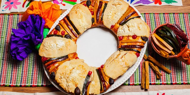 Golden Raisin Rosca De Reyes on a white platter sitting in the middle of a festively decorated table