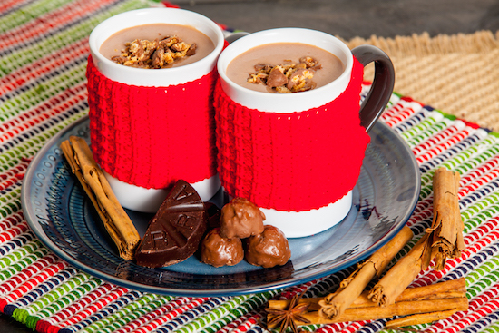 Two white and red mugs of Mexican hot chocolate sitting on a tray