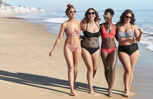 Four women on the beach wearing bikinis and one piece bathing suits
