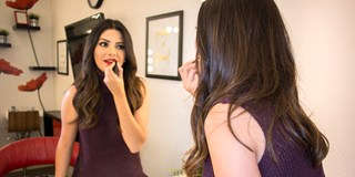 Ana Patricia applying lipstick in a mirror