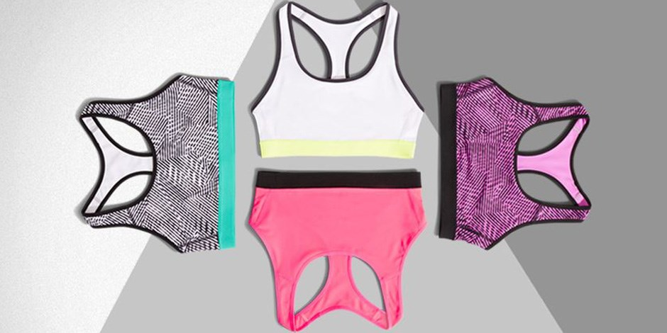 Four sports bras lying in a circle against a light grey and dark grey background
