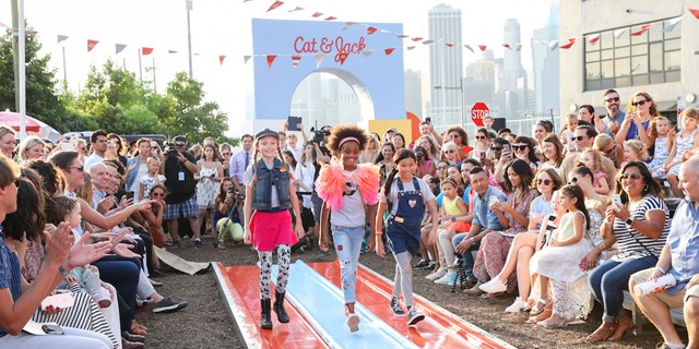 Three child models strutting down the Cat and Jack slide runway as celebrities look on