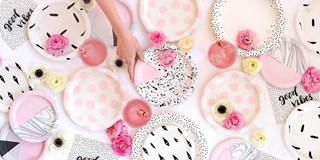 hand reaching for different patterned paper plates one a table with flowers, napkins, and glasses