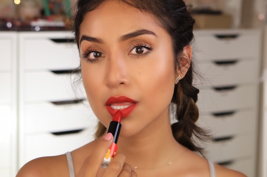 Dulce Candy applying red matte lipstick