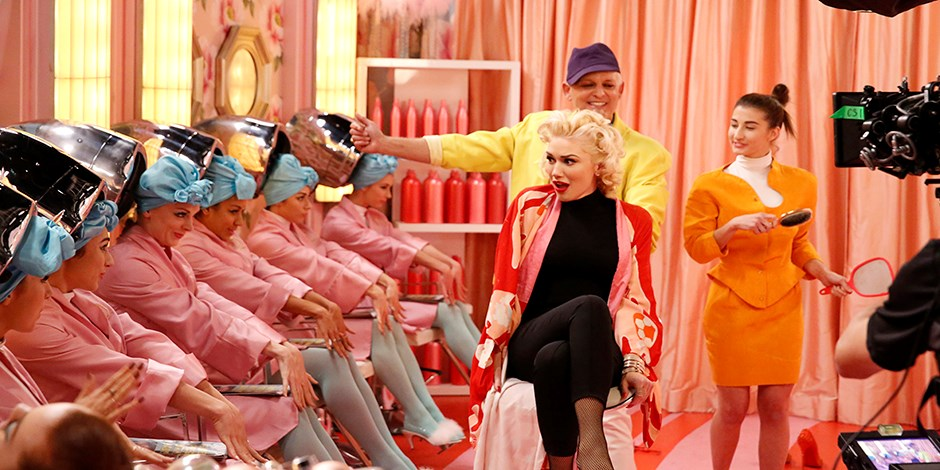 Gwen sitting in a pink beauty parlor with dancers and her stylist, while a camera films the action.