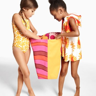 Two little girls, wearing Marimekko for Target swimwear and beachwear peek into a beach bag